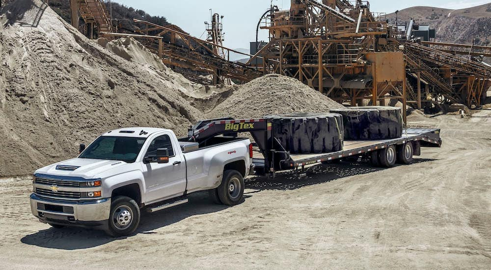 A silver 2017 Chevy Silverado 3500HD is towing a gooseneck trailer with two massive tires on it.