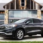 A dark gray 2019 used Buick Enclave Avenir is parked in front of a modern barn.