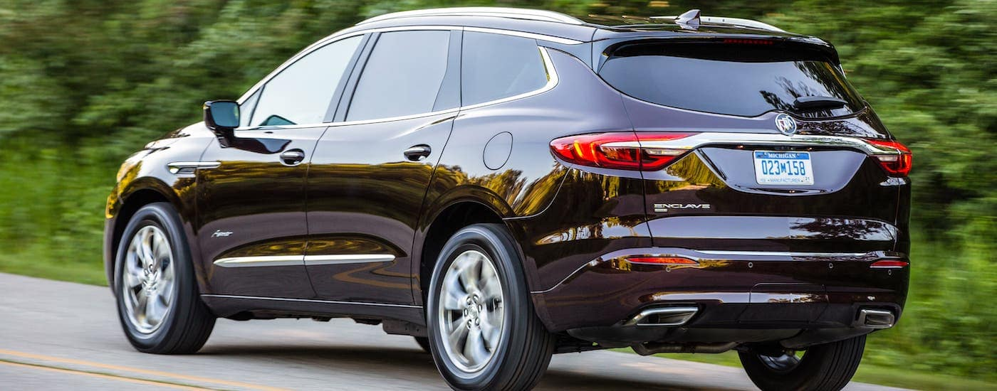 A burgundy 2019 Buick Enclave Avenir is shown from a rear angle while driving on a tree-lined road.