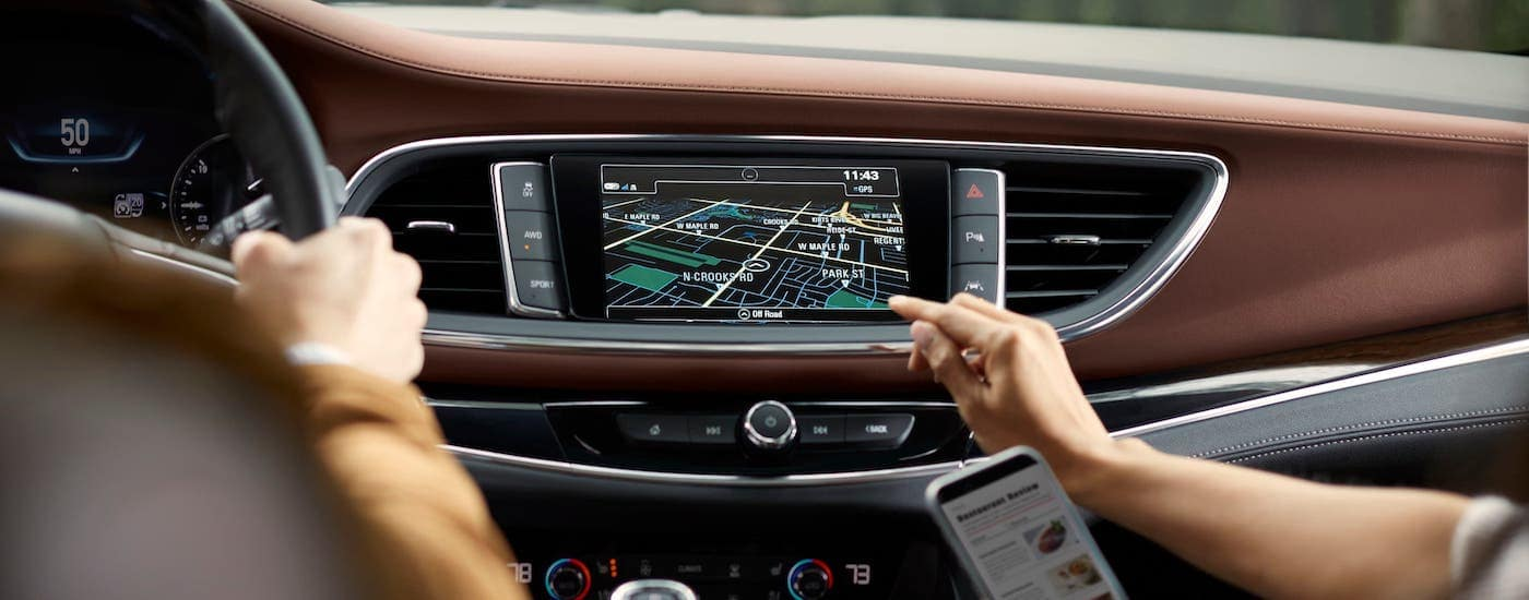 A passenger is using the infotainment screen in a 2019 Buick Enclave Avenir.