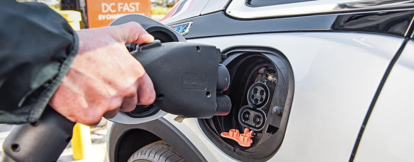 A closeup shows the charging port of a silver 2021 Chevy Bolt EV.
