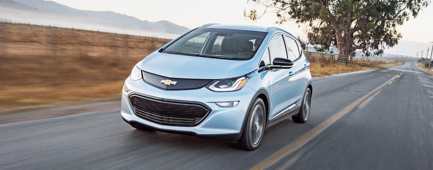 A silver 2021 Chevy Bolt EV is driving on a highway.