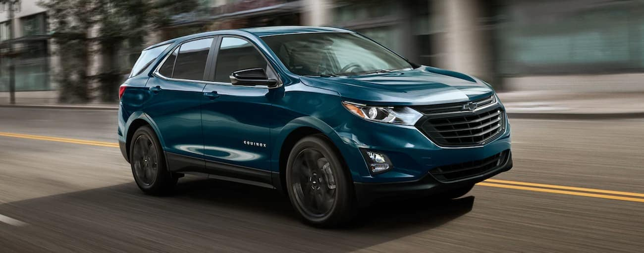 A blue 2021 Chevy Equinox is driving on a city street.