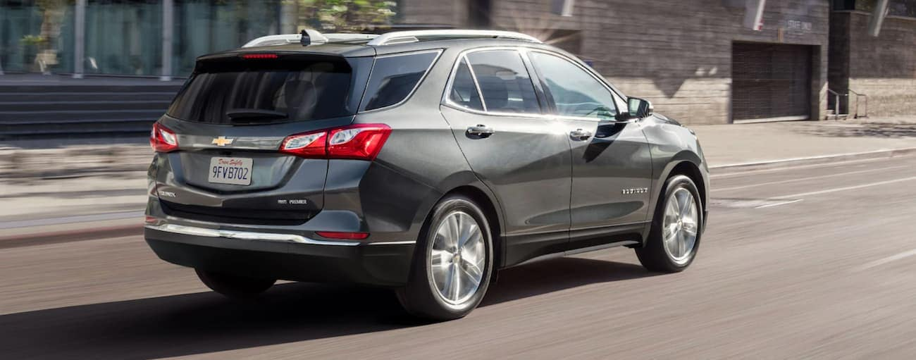 A grey 2021 Chevy Equinox is driving on a city street.
