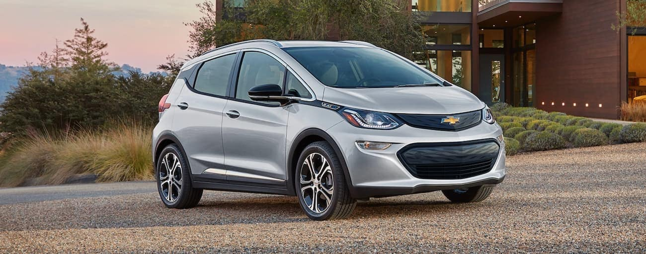 A silver 2021 Chevy Bolt EV is parked in a driveway at sunset.