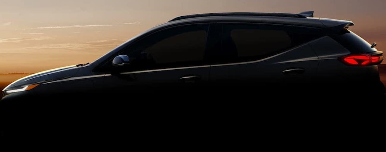 The silhouette of a 2022 Chevy Bolt EUV is shown from the side at sunset.