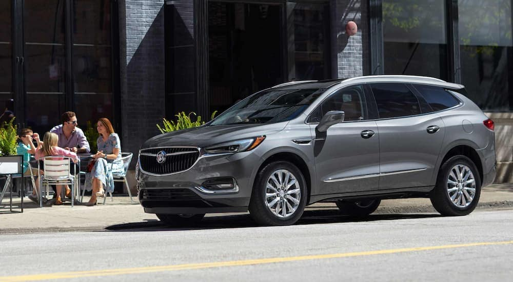 A grey 2021 Buick Envision is parked on a city street next to a family eating outside.