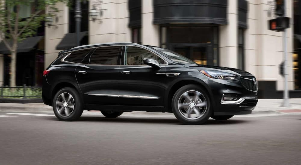 A black 2021 Buick Enclave is driving on a city street after leaving a Buick Enclave dealer near me.