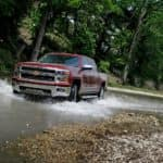A popular pre-owned Chevy truck, a burgundy 2014 Chevy Silverado LTZ, is driving through a stream.