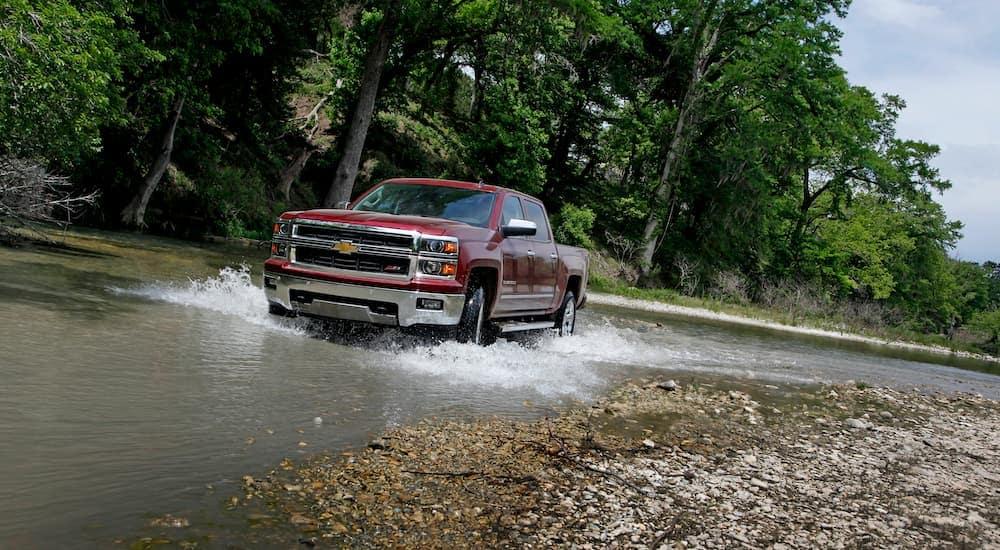 A popular pre-owned Chevy truck, a burgundy 2014 Chevy Silverado LTZ, is shown driving through a stream.