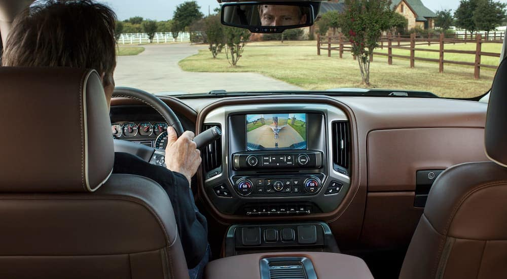 The brown interior and back up camera are shown in a 2018 Chevy Silverado High Country.