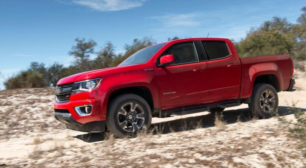 A red 2019 Chevy Colorado Z71 is driving on a sandy trail.