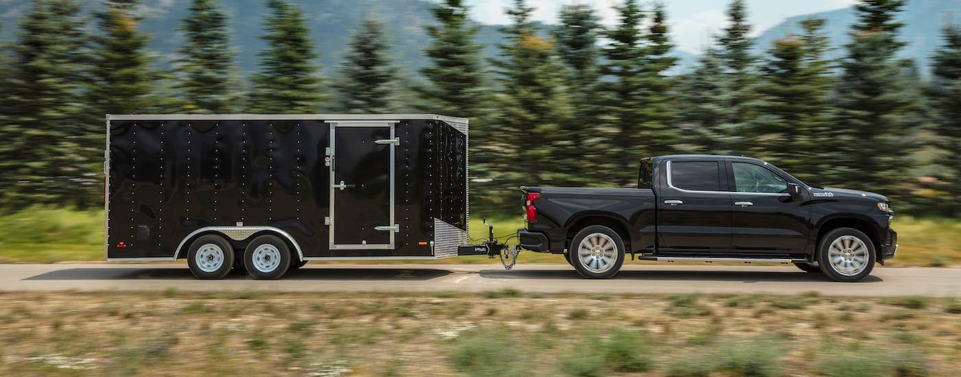 A black 2020 Chevy Silverado 1500 is shown from the side towing an en enclosed trailer.