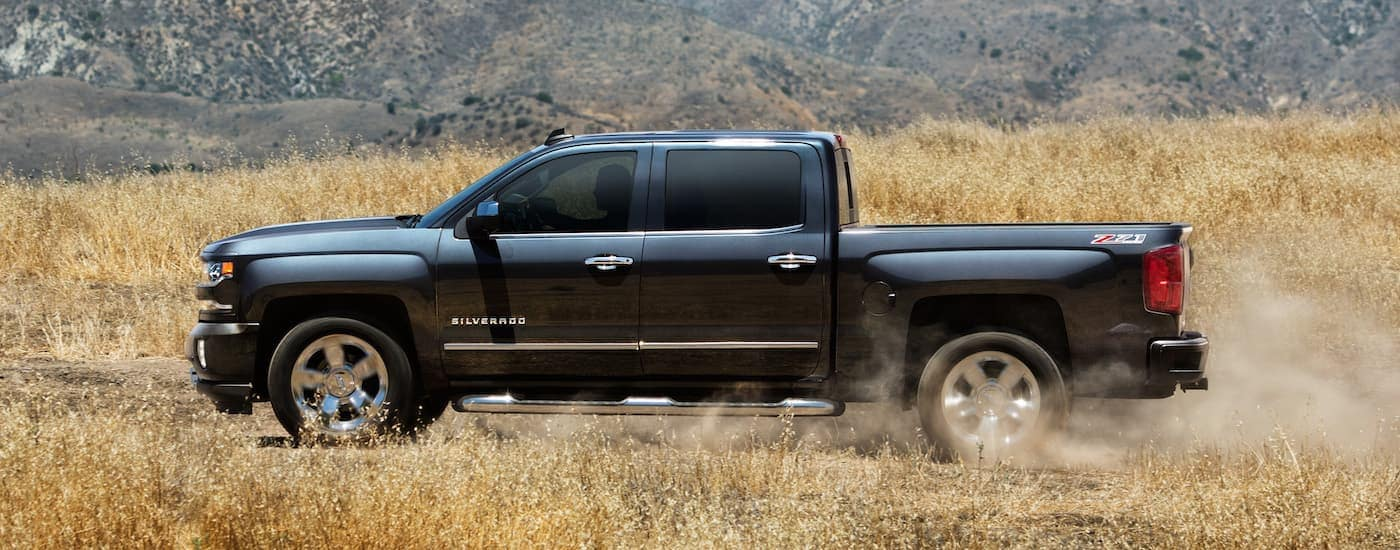 A dark grey 2018 Chevy Silverado 1500 is shown from the side driving in a field.