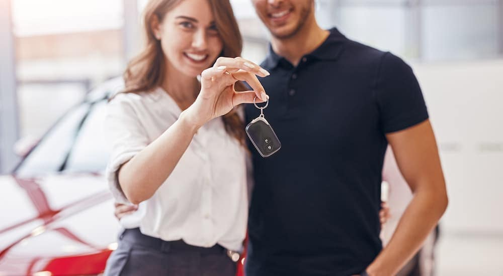 A couple is holding up a key fob at a used car lot near Lexington.