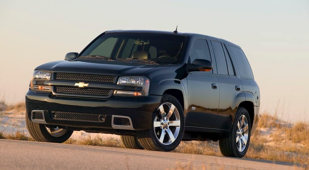 A black 2009 used Chevy Trailblazer is parked in front of sand dunes and beach grass.