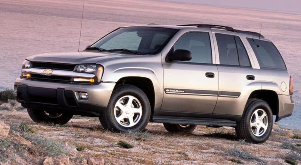 A tan 2009 used Chevy Trailblazer is parked in front of the ocean at sunset.