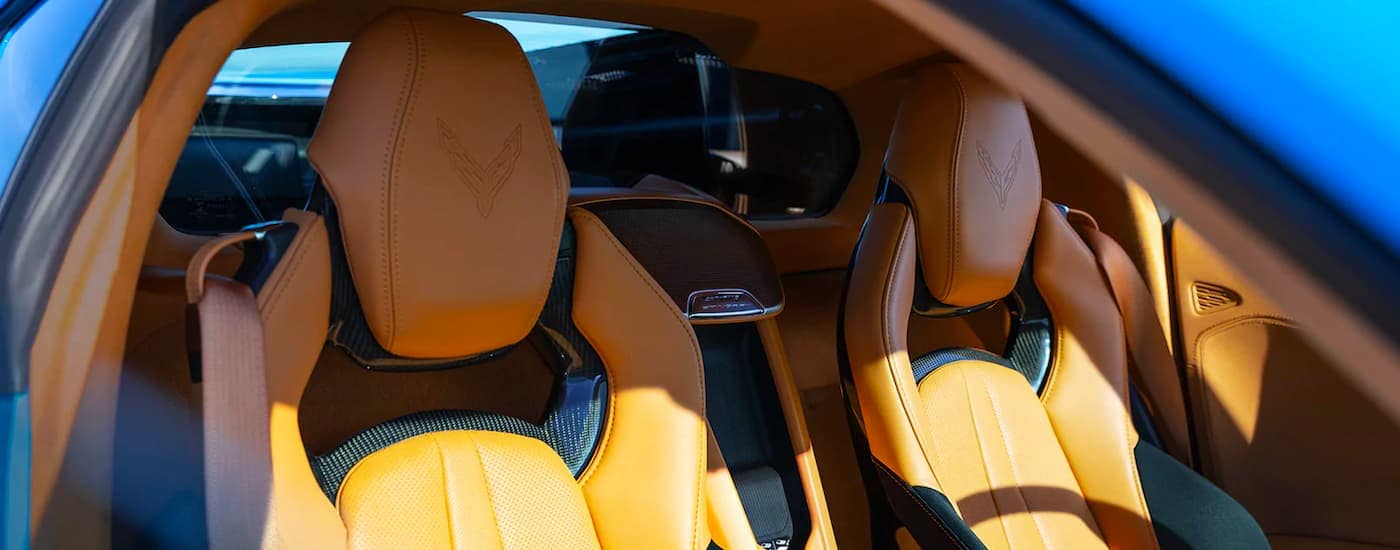 A close up shows the tan and black leather interior of a blue 2021 Chevy Corvette.