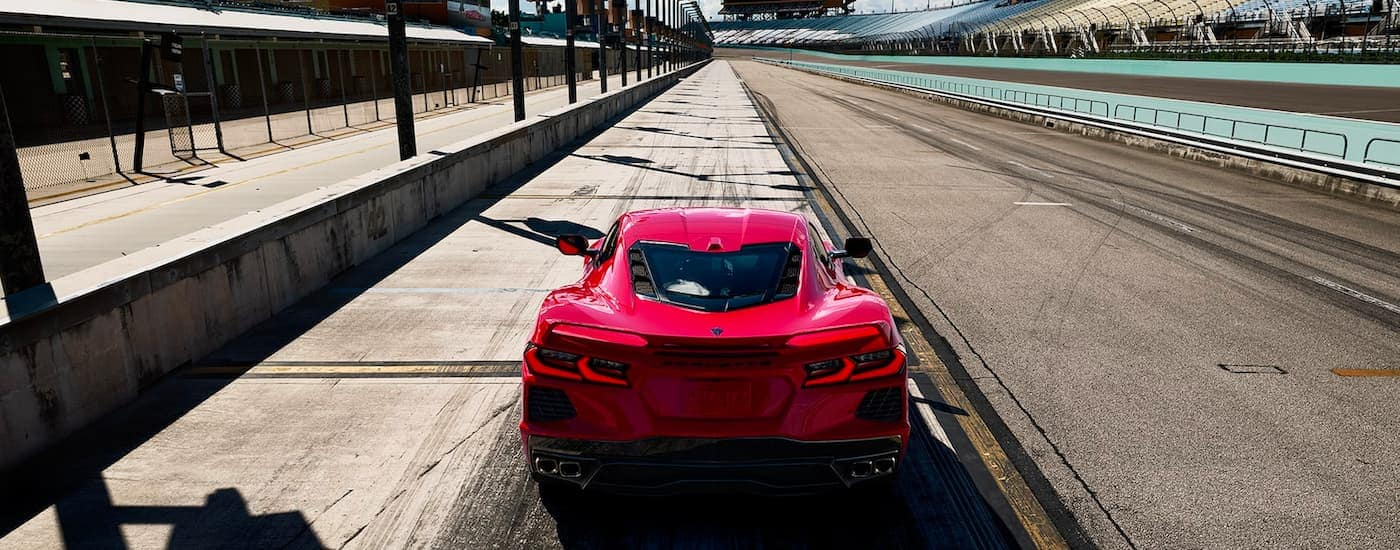 A red 2021 Chevy Corvette is shown from behind, from a high angle, ready to drive down a racetrack.