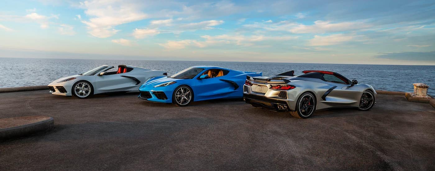 A white, a blue, and a silver 2021 Chevy Corvette are parked on a pier with the ocean and sky in the background.