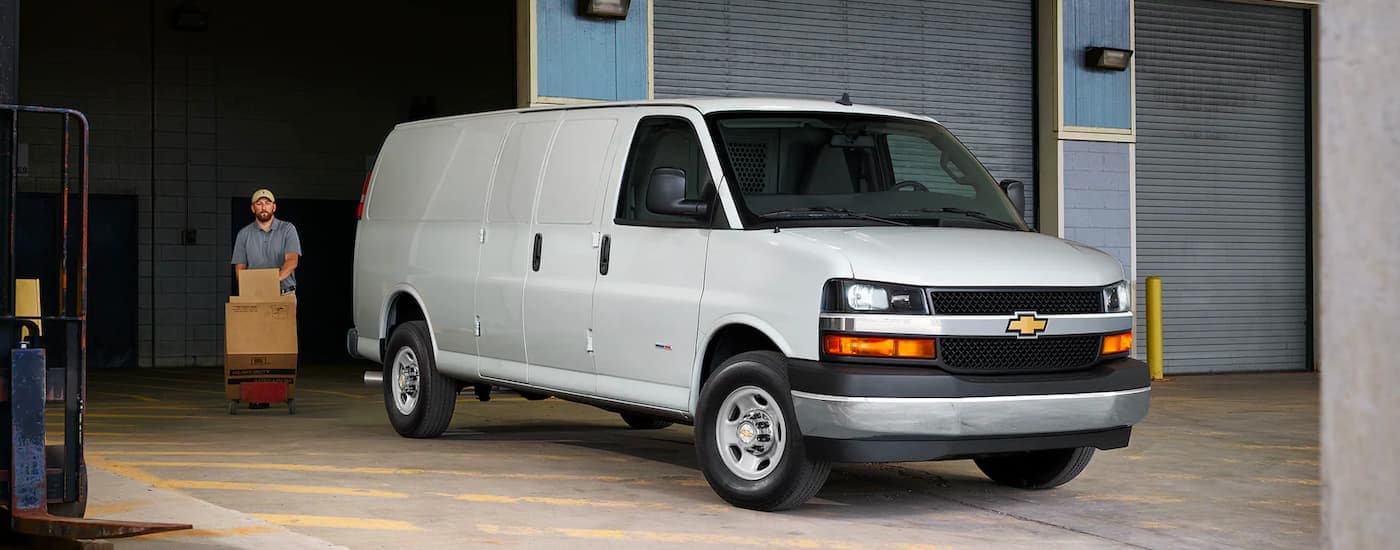 A white 2021 Chevy Express Van is parked on a warehouse dock next to an open bay door.