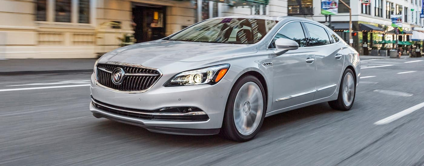 A silver 2017 Buick LaCrosse is driving past a city building.