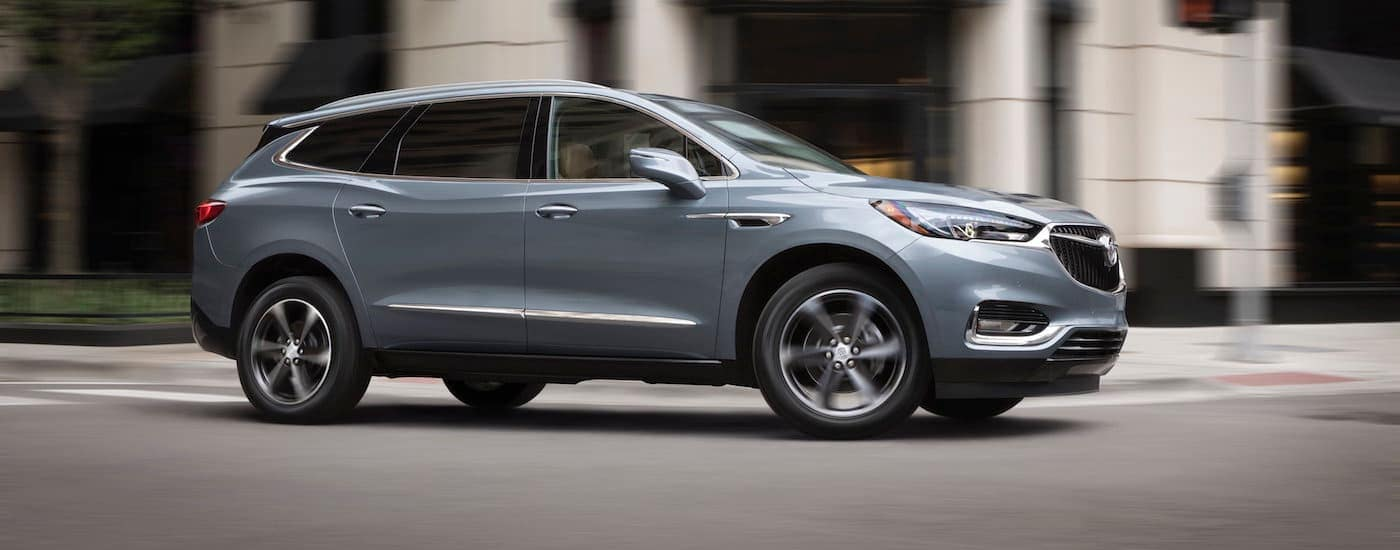 A grey 2018 Buick Enclave is driving through a city intersection.
