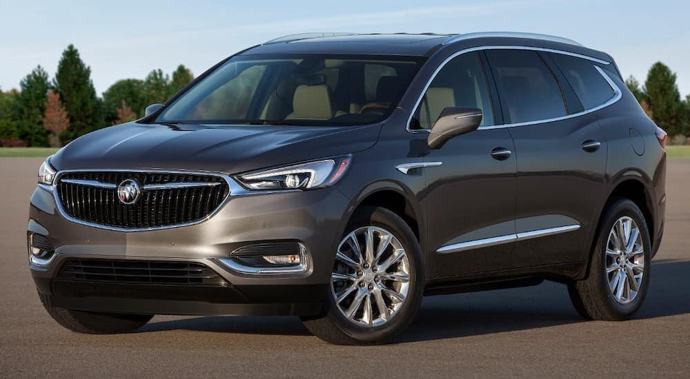 A grey 2018 Buick Enclave is parked in an open lot.
