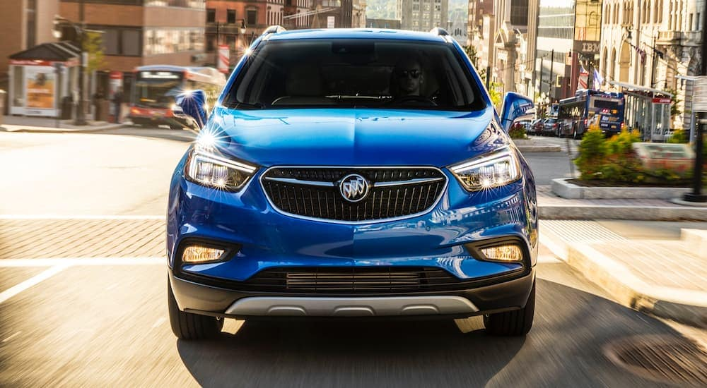 A blue 2018 Buick Encore is shown from the front on a city street after leaving a Lexington used Buick dealer.