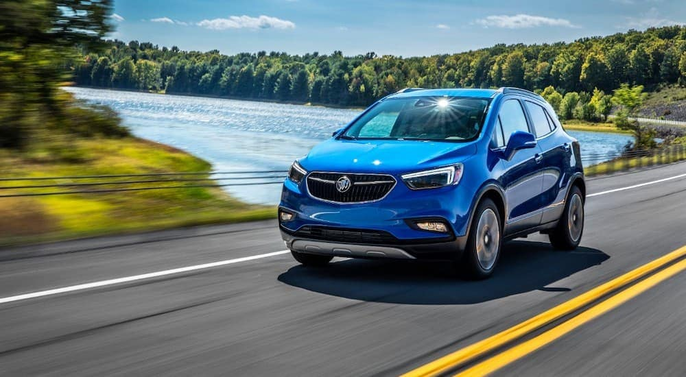 A blue 2018 Buick Encore is driving past a lake.