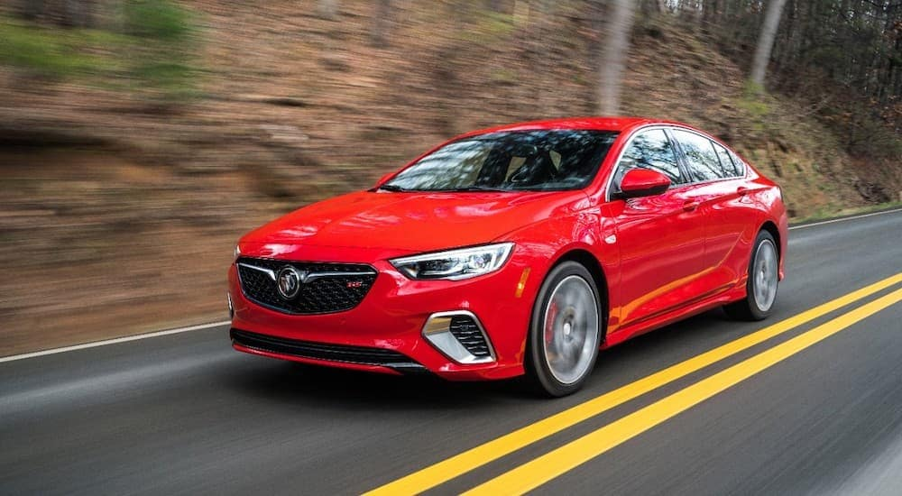 A red 2019 Buick Regal GS is driving past woods after leaving a Lexington used Buick dealership.