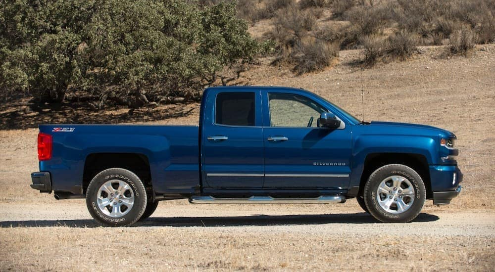 A blue 2018 Chevy Silverado 1500 is shown from the side on a dirt road with dry grass.