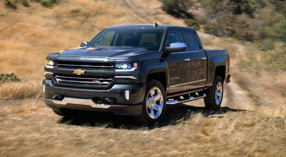 A grey 2018 Chevy Silverado is driving on a path in a field after leaving a Lexington used Chevy dealer.