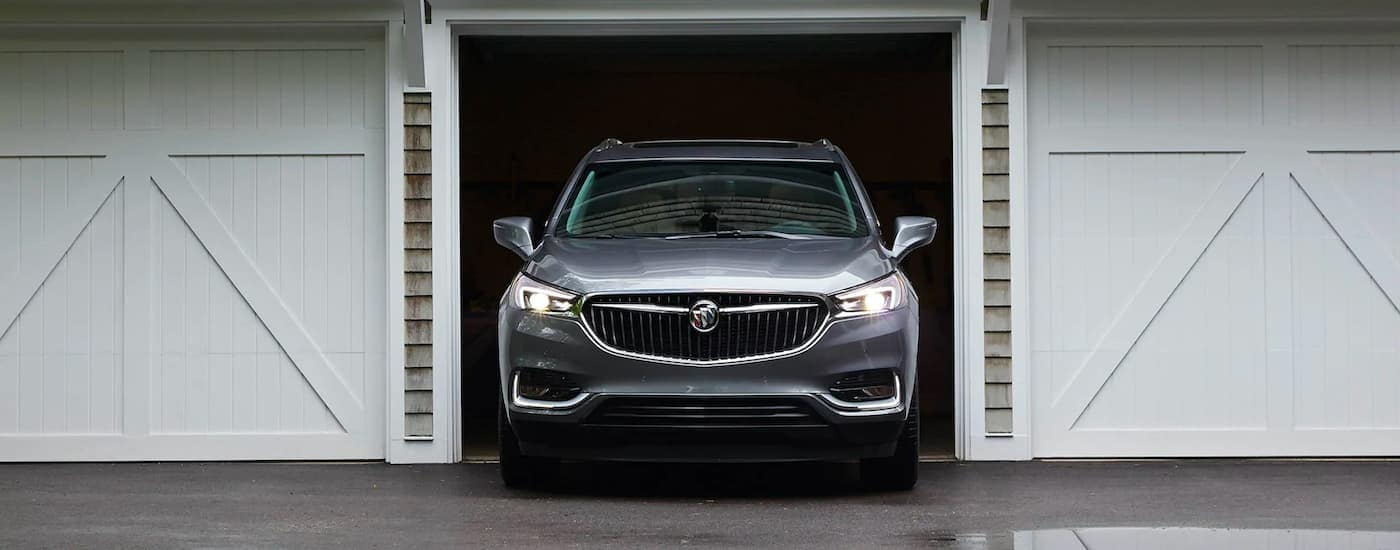 A gray 2021 Buick Enclave is shown pulling out of a garage.