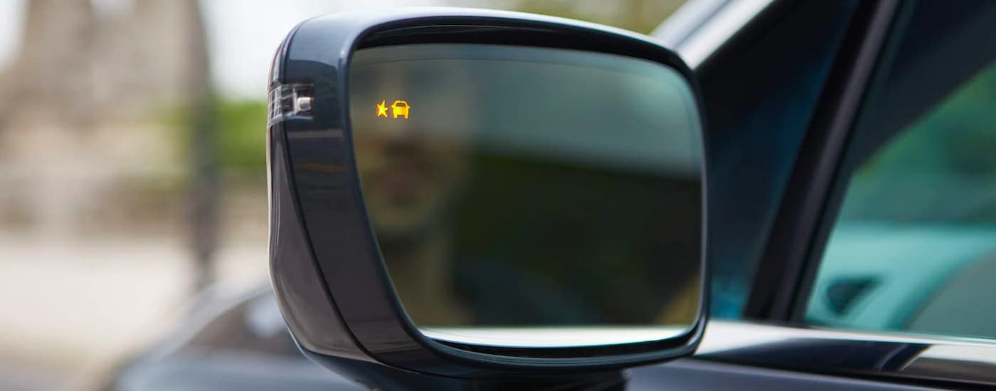 The blind spot monitoring icon is shown on the mirror of a 2021 Buick Enclave.