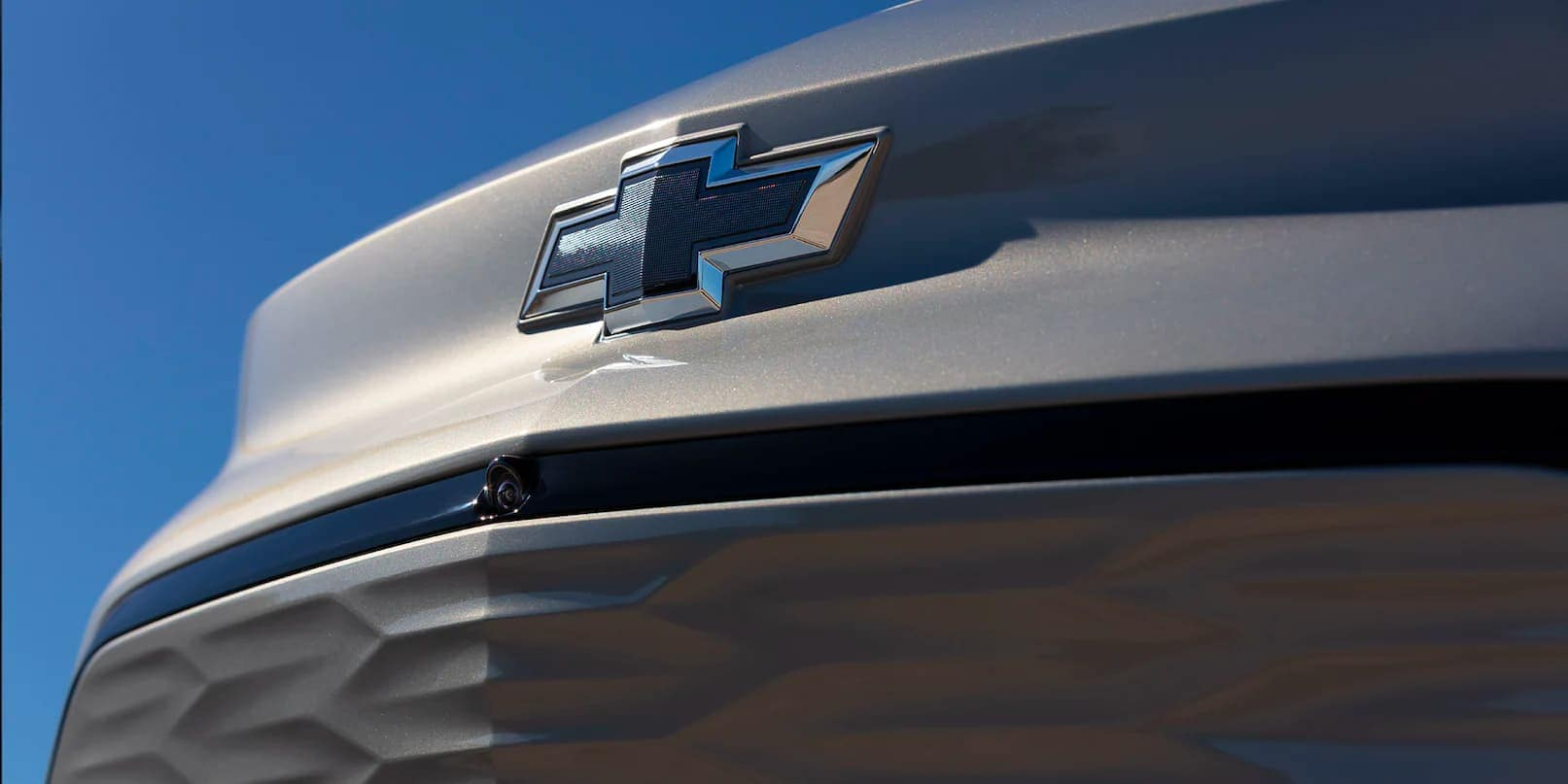 A close up shows the bowtie emblem on the front of a silver 2022 Chevy Bolt EUV.