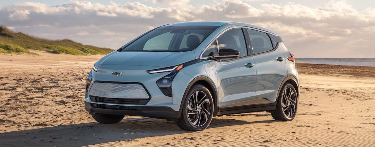 A light blue 2022 Chevy Bolt EV is parked on sand at the beach.