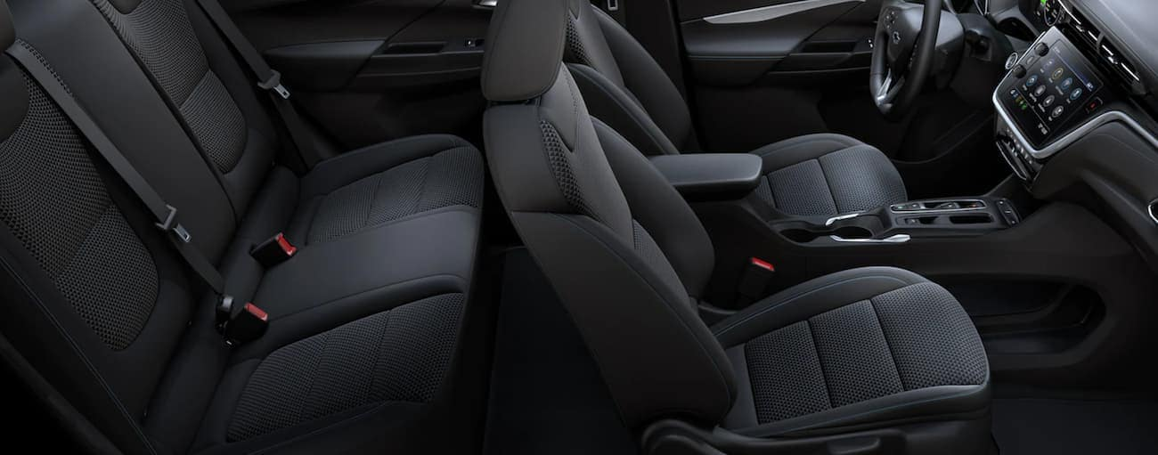 The black interior of a 2022 Chevy Bolt EV is shown from the side.