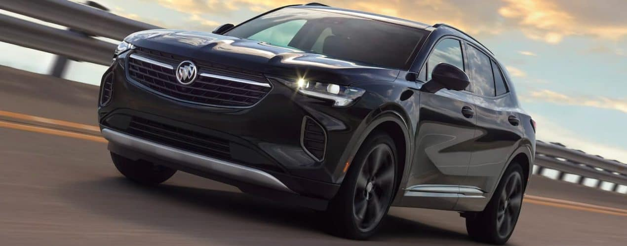 A black 2021 Buick Envision is shown from the side driving down an empty highway after winning the 2021 Buick Envision vs 2021 Acura RDX showdown.