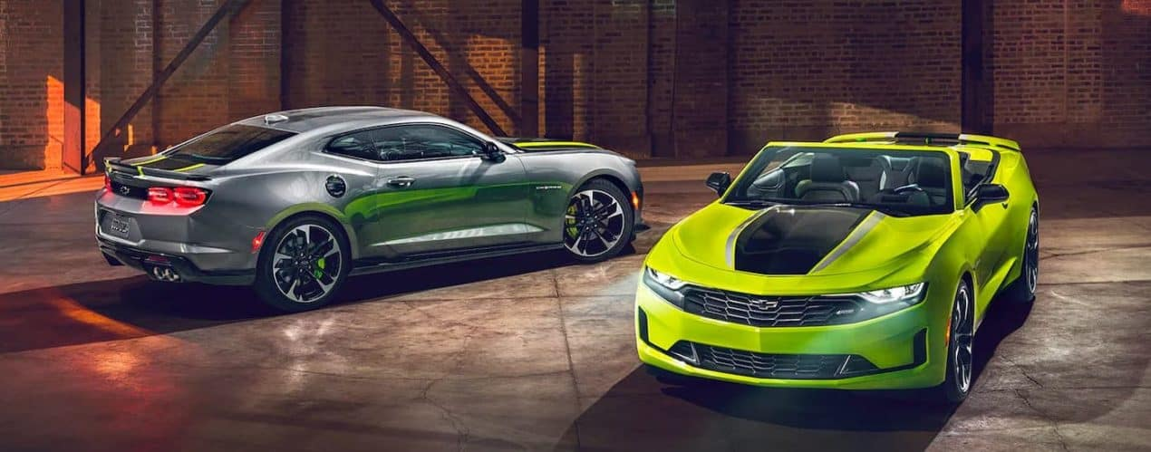 A silver 2021 Chevy Camaro 2SS and a green 3LT RS Shock and Steel Edition are shown parked in a warehouse.