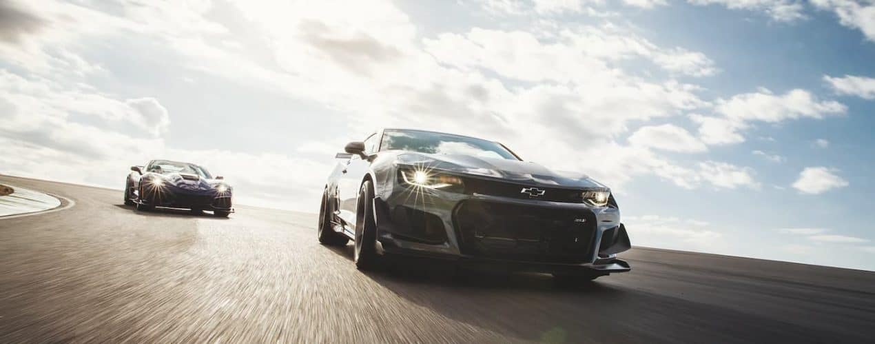 A black 2021 Chevy Corvette ZR1 and a black 2021 Camaro ZL1 are driving down a racetrack.