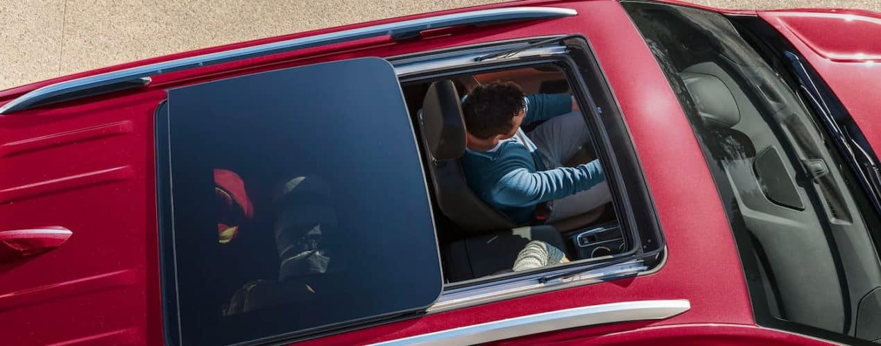 A close up shows the driver through the moonroof of a red 2021 Chevy Equinox after winning the 2021 Chevy Equinox vs 2021 Mazda CX-5.