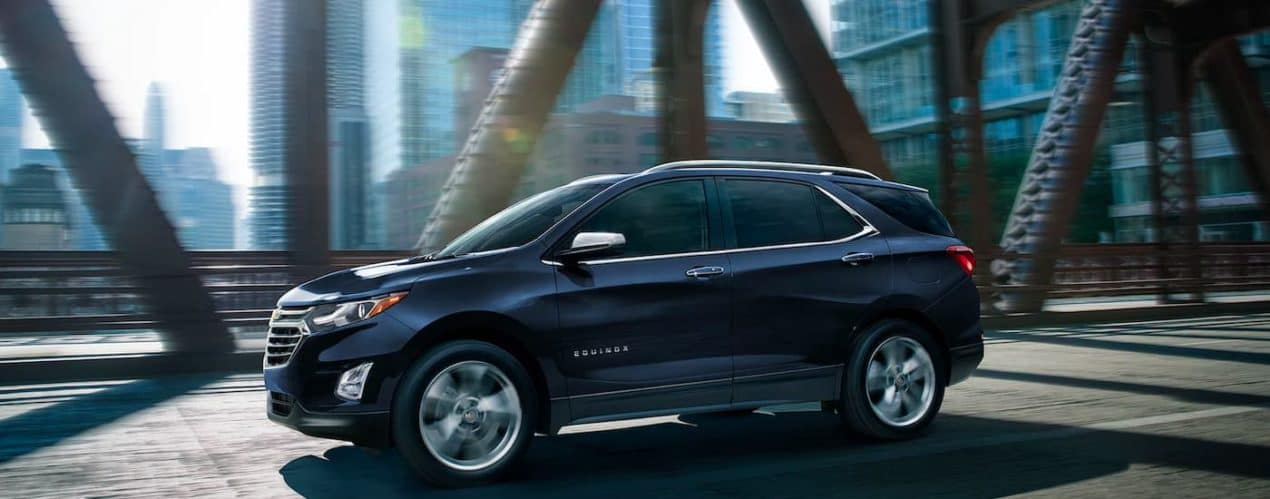 A dark blue 2021 Chevy Equinox is shown from the side driving down a steel bridge in a city after winning the 2021 Chevy Equinox vs 2021 Nissan Rogue battle.