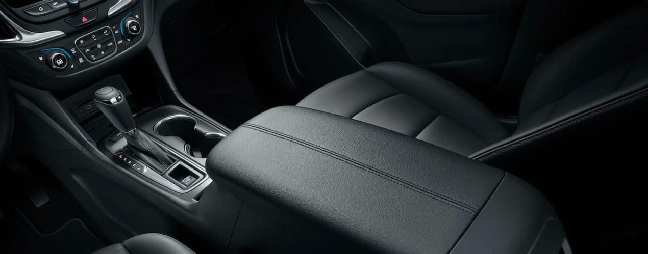 A close up shows the black leather interior and center console in a 2021 Chevy Equinox.