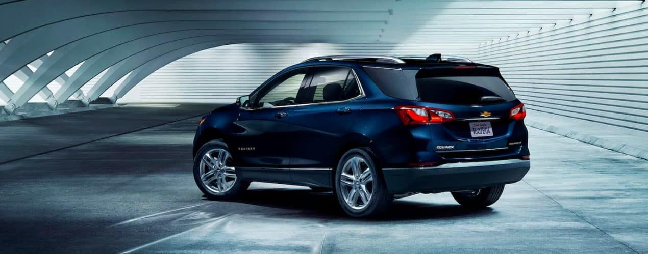 A dark blue 2021 Chevy Equinox is shown from the rear in a parking garage.