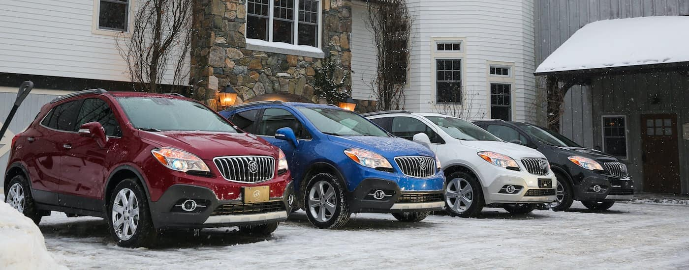 A red, a blue, a silver, and a black 2016 Buick Encore are shown parked in front of a cabin in the snow.