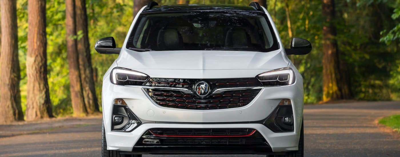 A white 2020 Buick Encore GX ST is shown from the front parked on a tree-lined road after leaving a used Buick dealership in Kentucky.