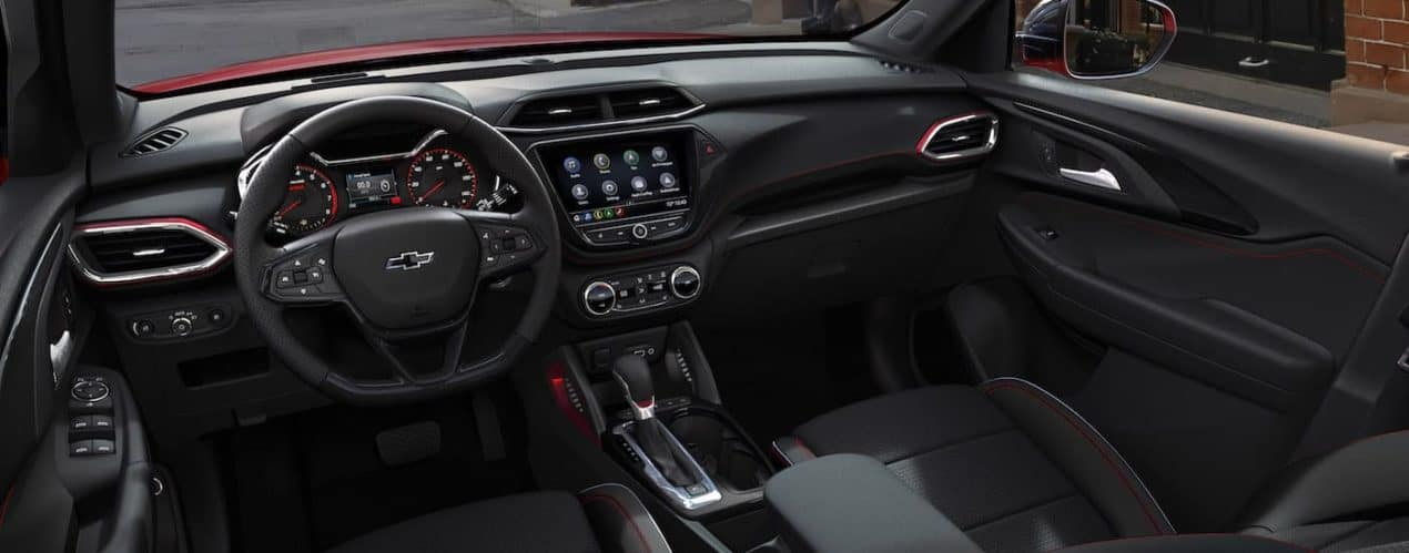The black interior and front seats are shown in a red 2021 Chevy Trailblazer RS.