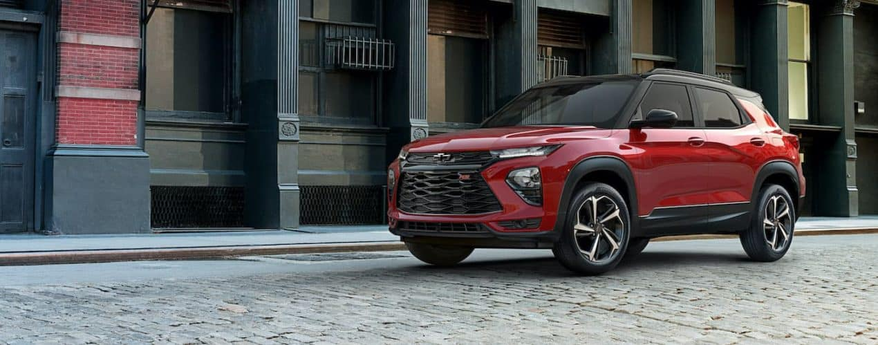 A red 2021 Chevy Trailblazer RS is shown from the side parked on a cobblestone street.