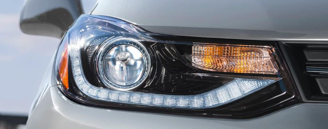 A close up shows the passanger headlight on a silver 2022 Chevy Trax.